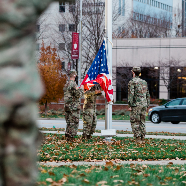 Three soldiers raise the American flag