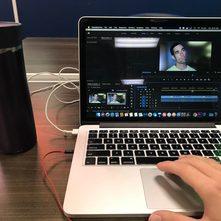 A tumbler of coffee sits to the left of a laptop that shows a video being edited.
