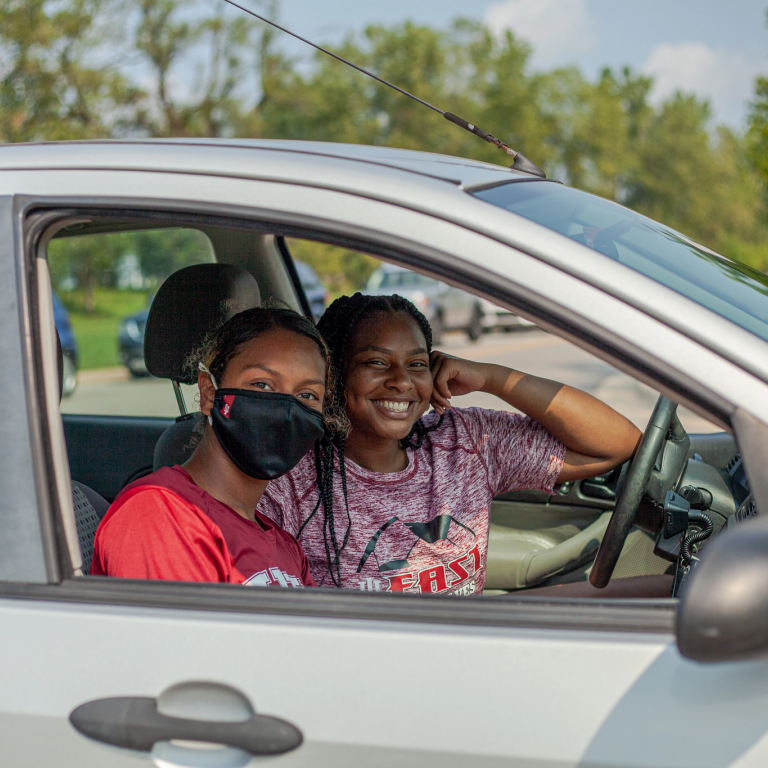 a person smiling and a person wearing a mask look out a car window
