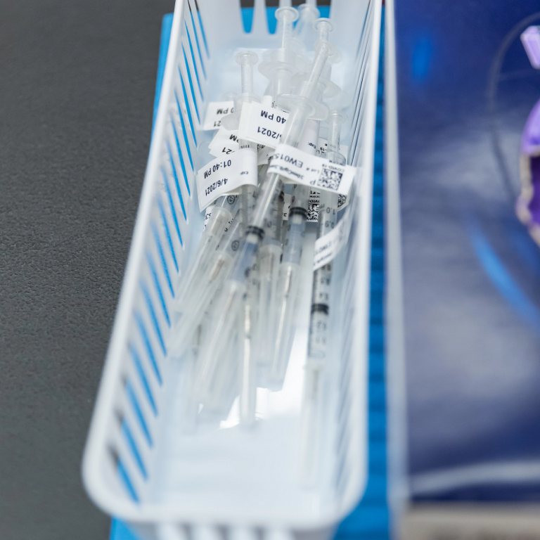 A collection of empty syringes in a white basket