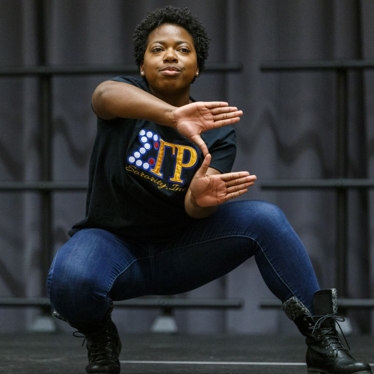 A member of Sigma Gamma Rho Sorority performs at the Yard Show, displaying her sorority's sign