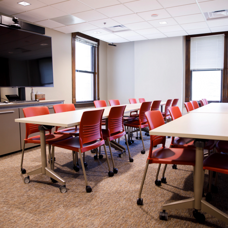 A conference room space, red chairs pushed under two long tables and a large TV on the wall