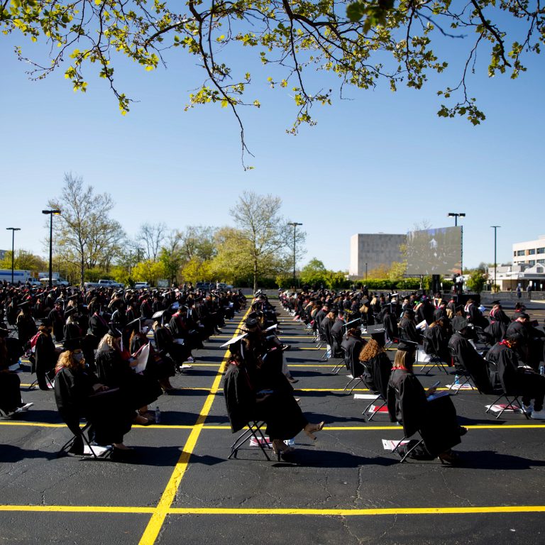 Graduates are seated in rows of chairs in a parking lot