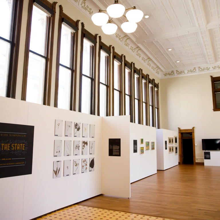 A new gallery space with art hanging on the walls and a bank of windows above it