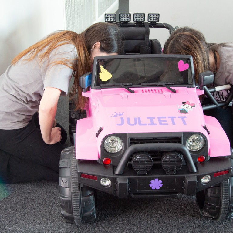 IUPUI students work on a pink car