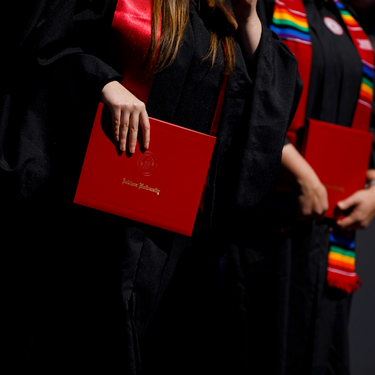 A close-up of graduates holding red Indiana University diploma covers