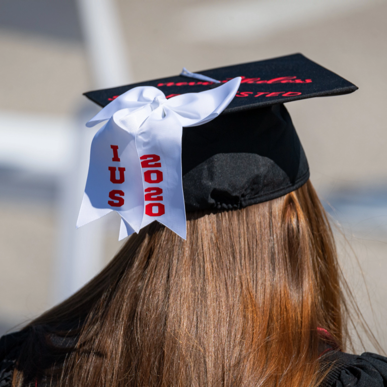 A white bow on the back of a graduation cap is decorated with 'IUS 2020'