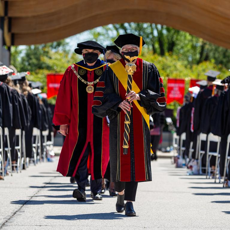 Members of the platform party walk between rows of graduates