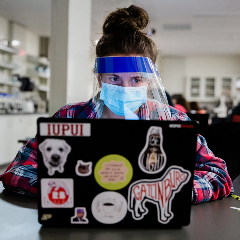 a student wearing a face mask and shield works on their computer