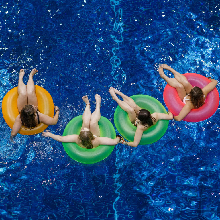 Four women sit in inner tubes in a pool