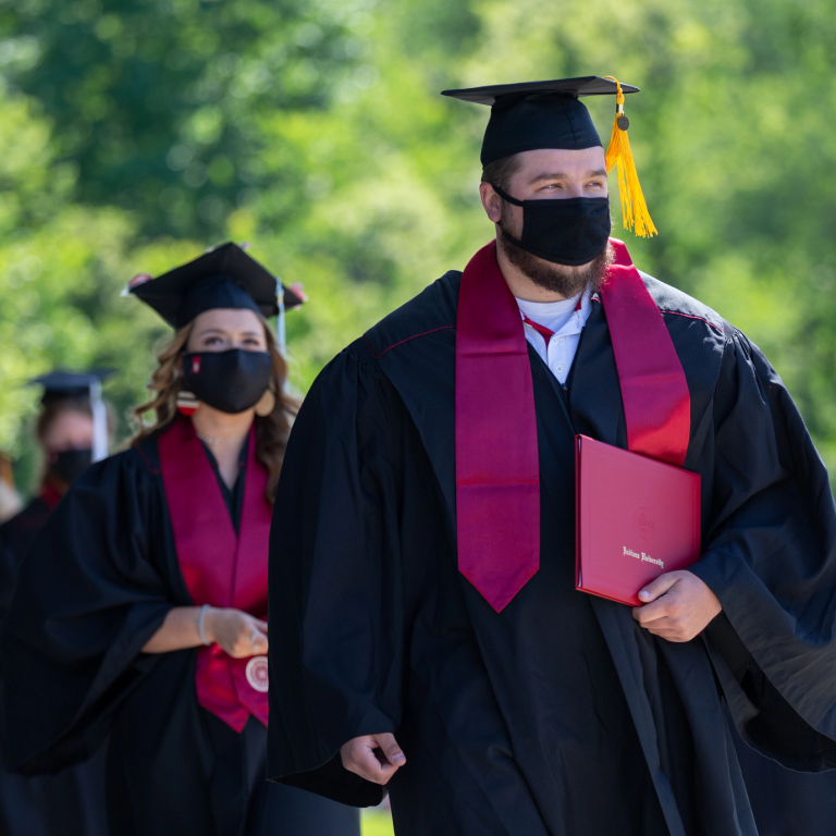 Masked graduates walk in a line holding their diplomas