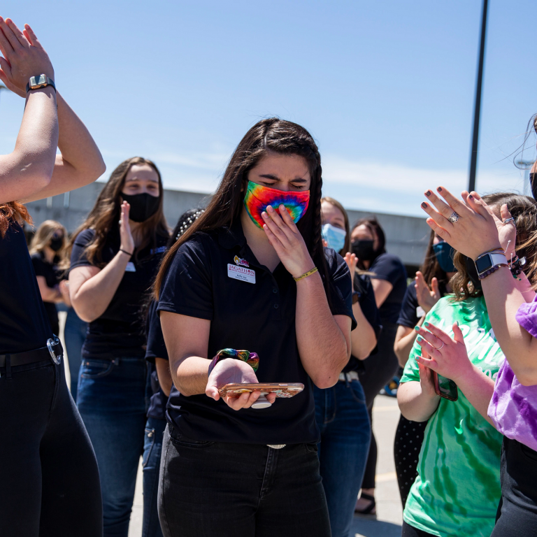 Students applaud a girl holding a cell phone.