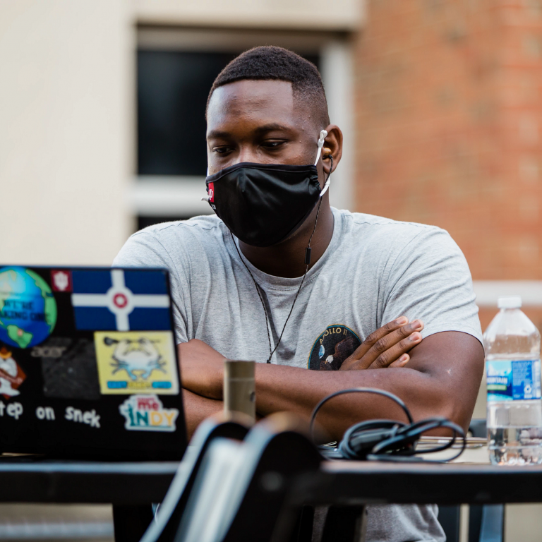 a student wearing a mask sits outside looking at his laptop