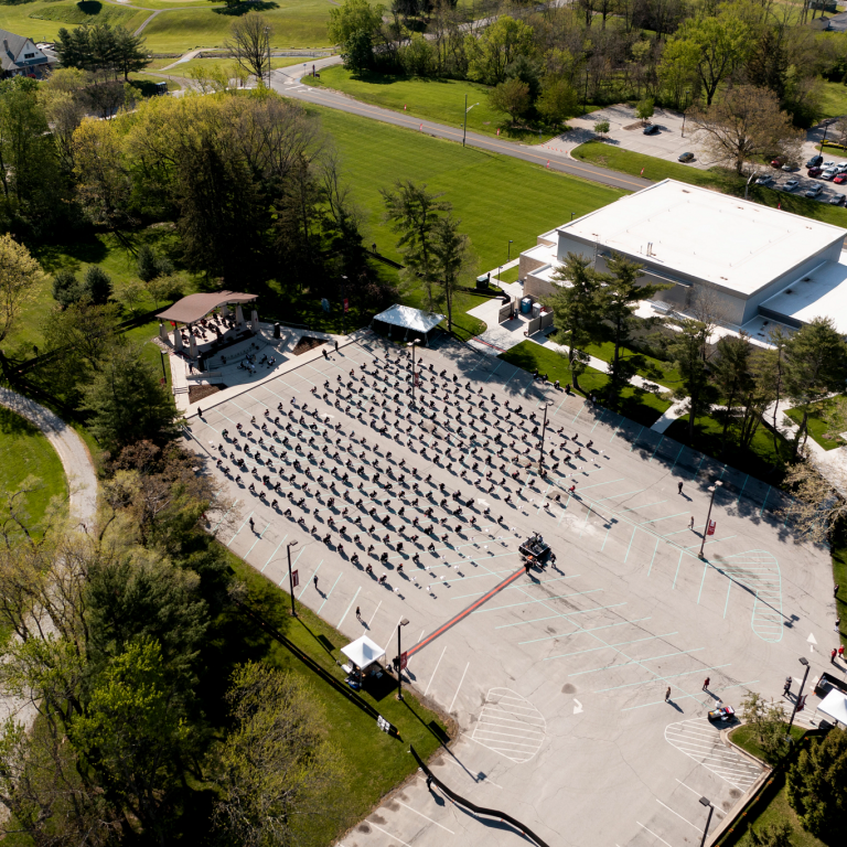 A drone shot from above of graduates sitting in a parking lot near the IU Kokomo Pavilion