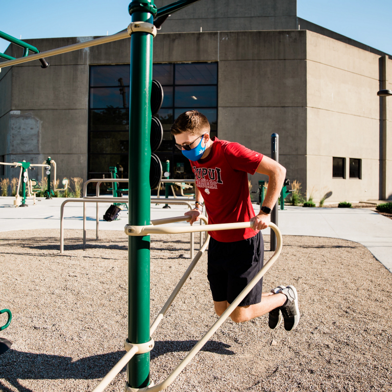 a person uses outdoor fitness equipment for dips