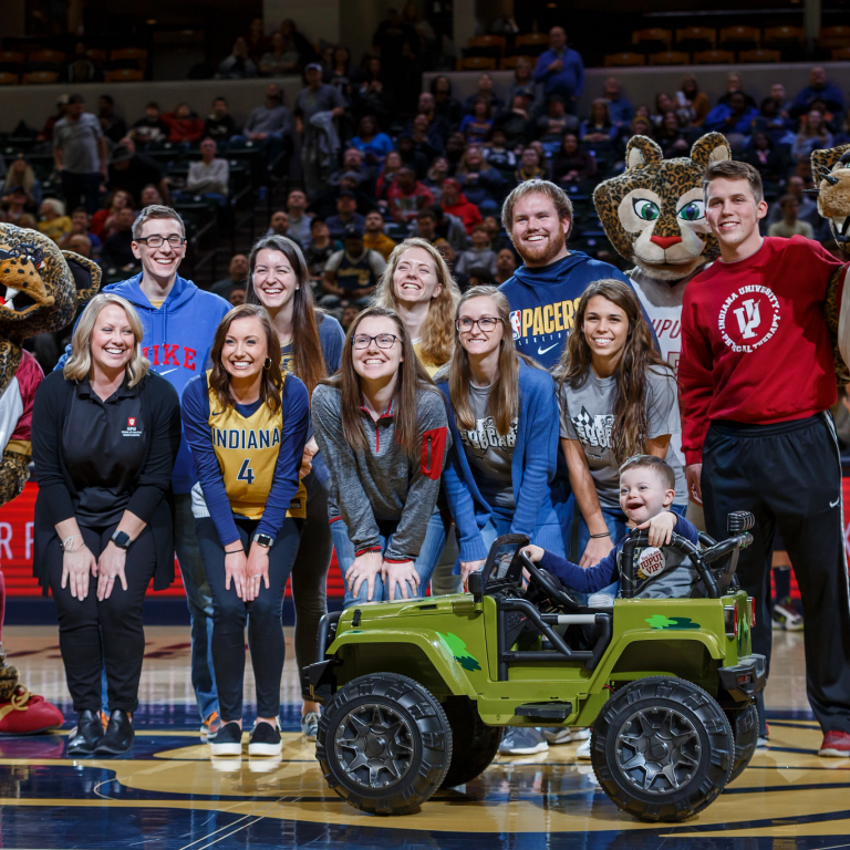 10 people, one kid and three IUPUI mascots pose for a picture on the Indiana Pacers court