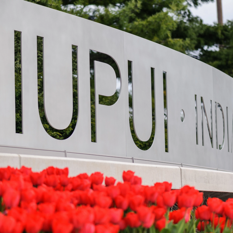 IUPUI's gateway sign with red tulips in full bloom in the foreground