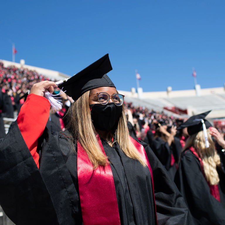 A masked graduate in a cap and gown turns the tassel on her graduation cap