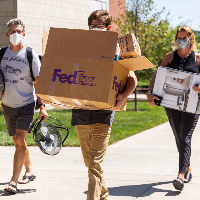 a student and two parents wearing masks carry things in on move-in day
