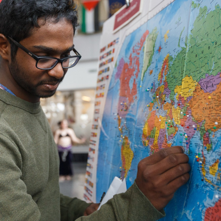 An IUPUI student pins his hometown on the board at the 2020 IUPUI International Festival.