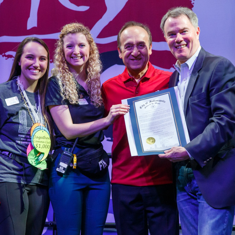Two IUPUI students, chancellor Paydar and Indianapolis mayor Joe Hogsett pose with a proclamation