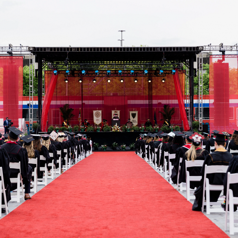 Graduates sit in rows of white chairs facing a stage decorated in crimson