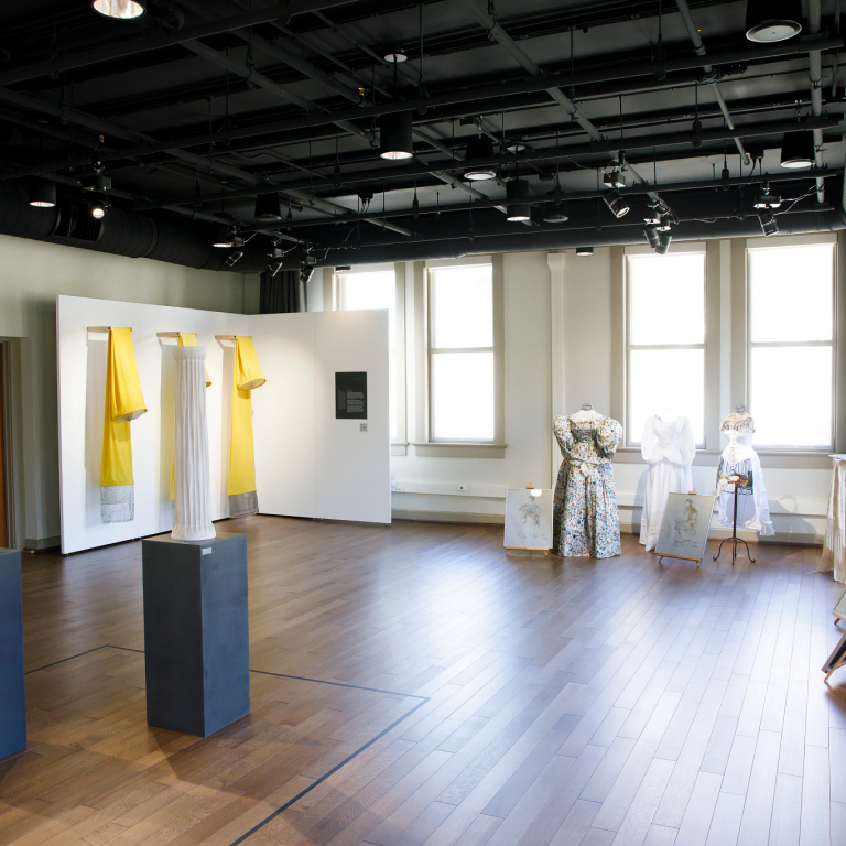 A new gallery space has paintings, sculptures and vintage dresses on mannequins