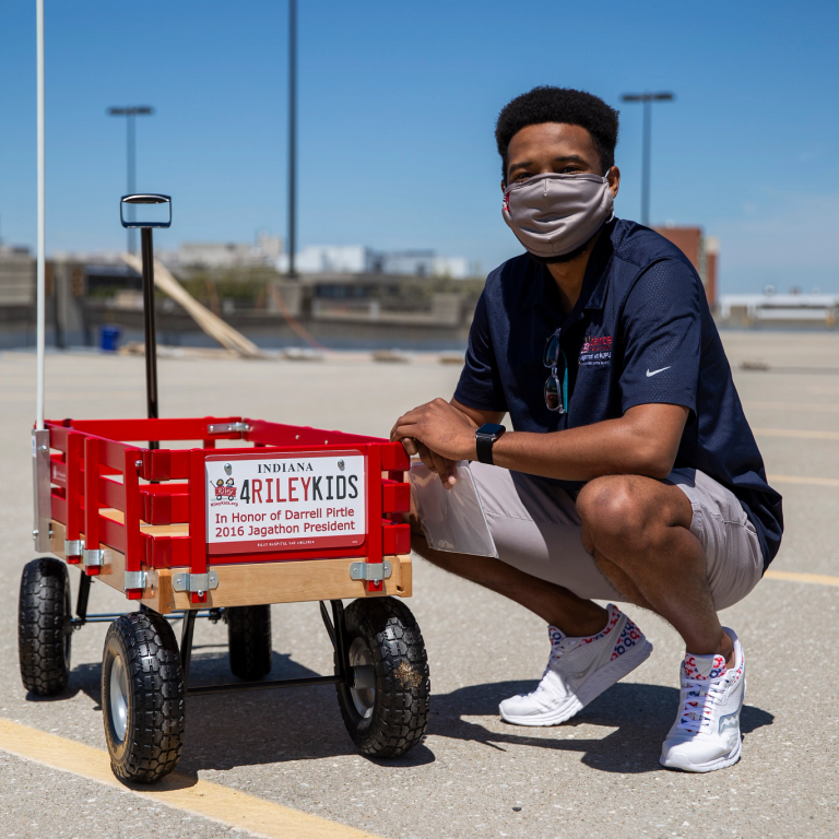 Darrell Pirtle kneels next to wagon with a sign in his honor.