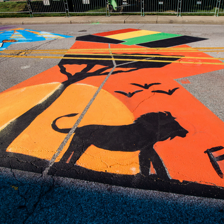 a silhouette of a lion and tree painted in one of the letters of the Black Lives Matter mural
