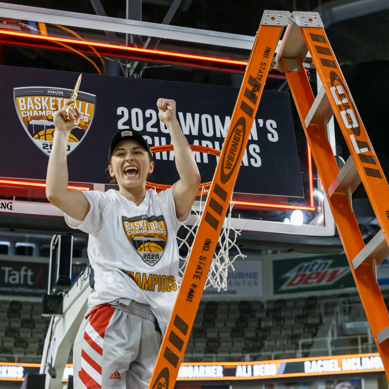 A woman stands on a ladder with a piece of net cut from a basketball goal