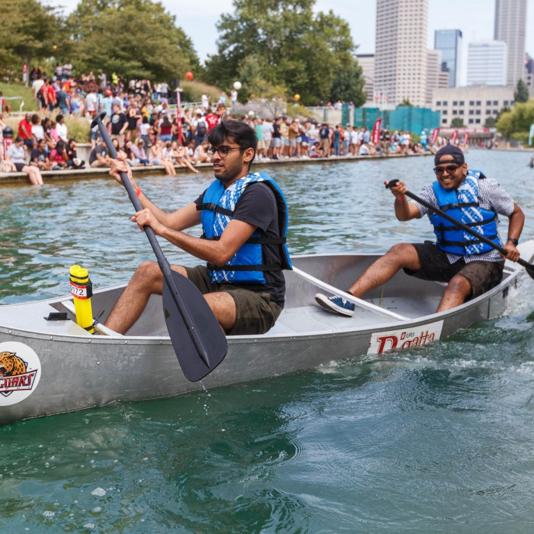 A canoe team paddles vigorously to keep from tipping their boat over.