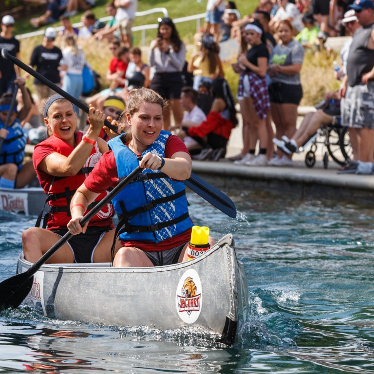 Two participants paddle their canoe up the canal in the women's division race.