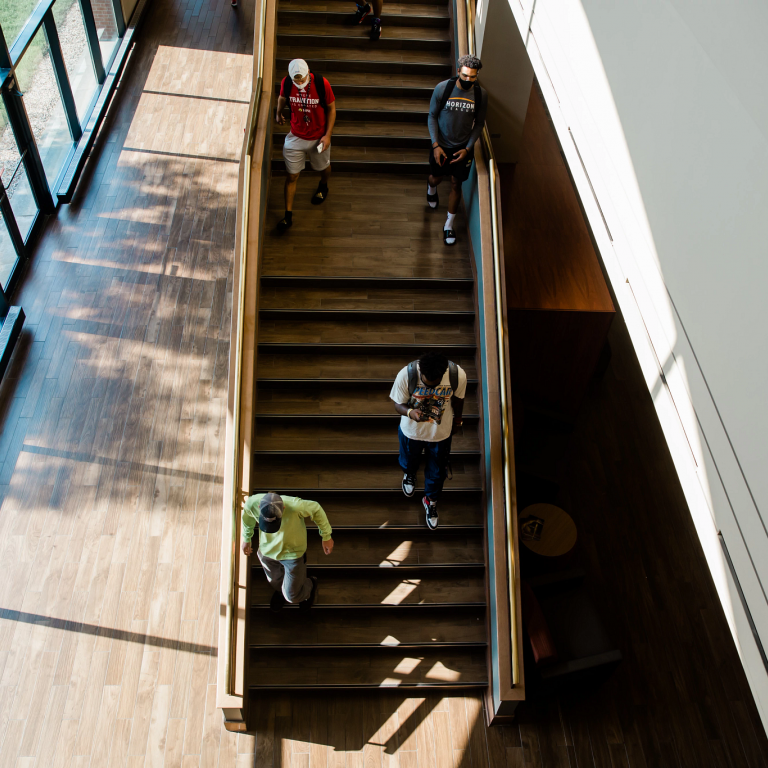 four students walking down a staircase