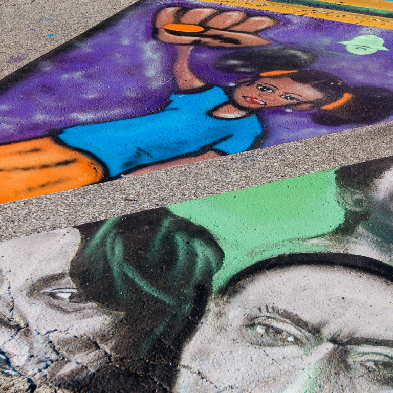 three faces painted on a street mural