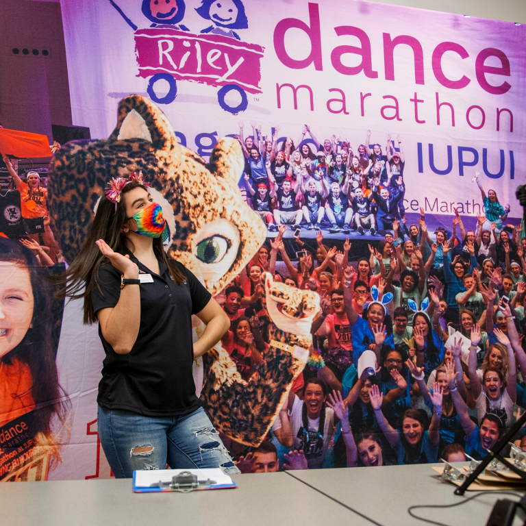 Student stands in front of Jagathon banner and a camera.