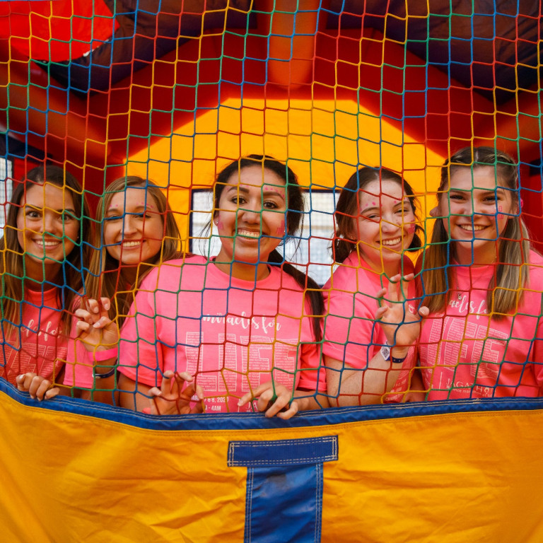 IUPUI students in pink T-shirts stand in a bounce house, looking through the net