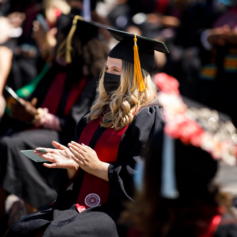 A graduate claps while seated in a line next to other graduates