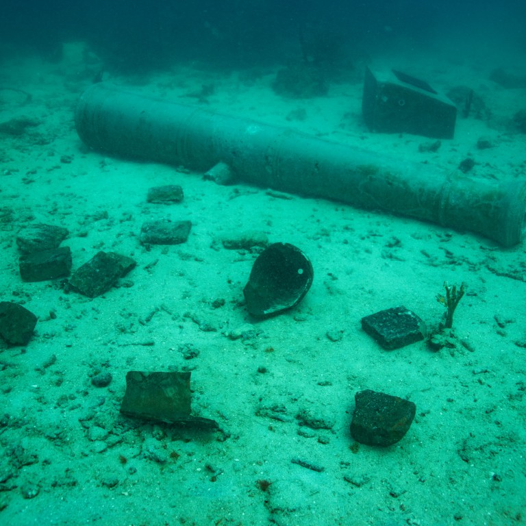 Artifacts including ceramics and a replica cannon pictured on the sea floor