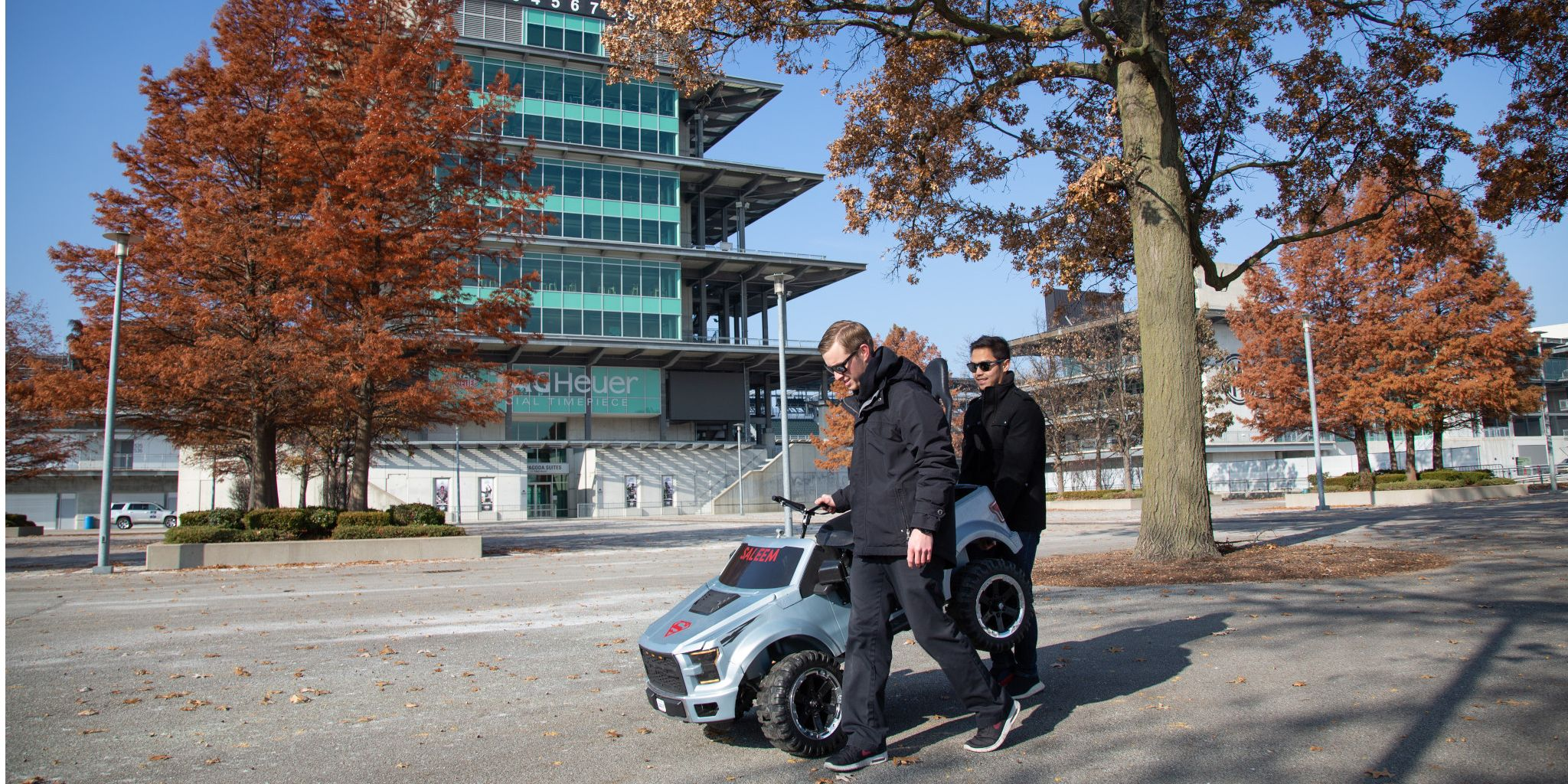 IUPUI students carry a silver car into the GoBabyGo event at the Indianapolis Motor Speedway