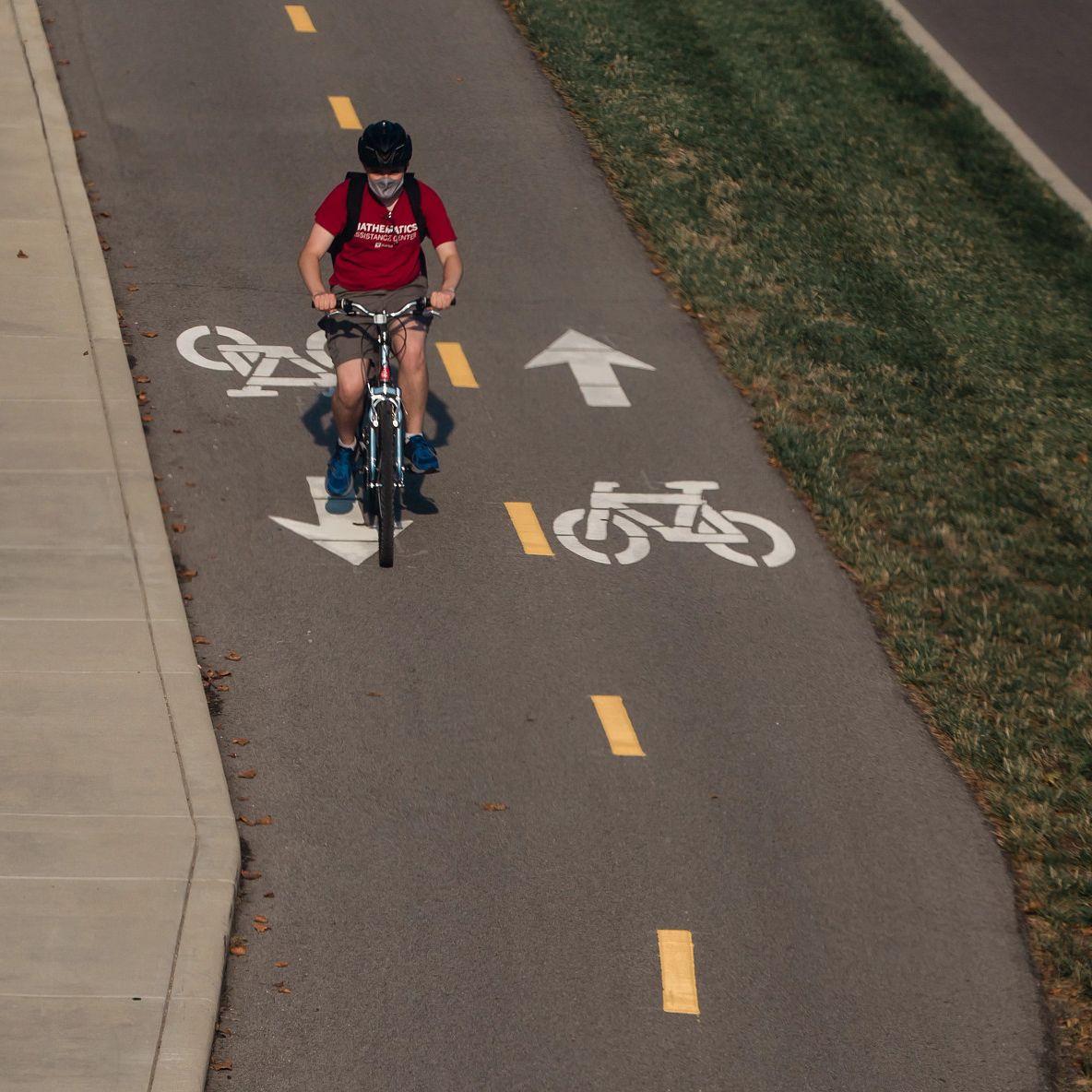 student riding a bike in a bike lane
