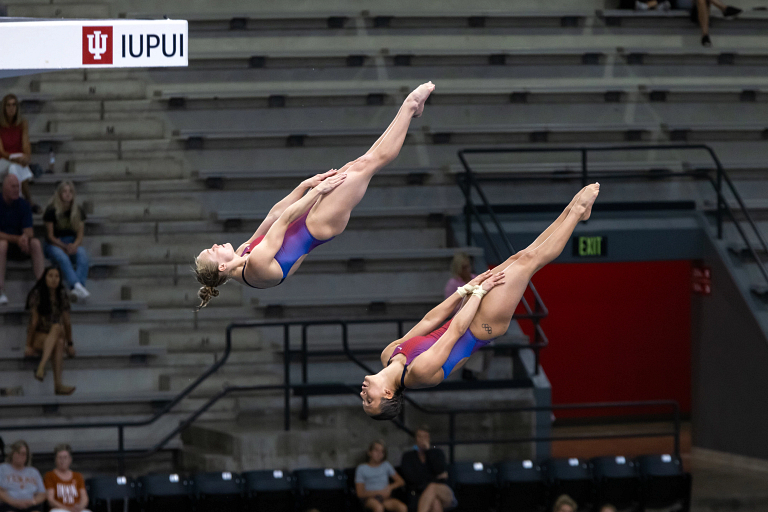 Two divers twisting through the air