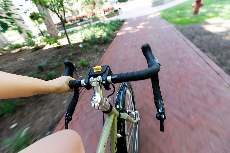 A closeup of handlebars from the cyclist's perspective while riding on a brick path