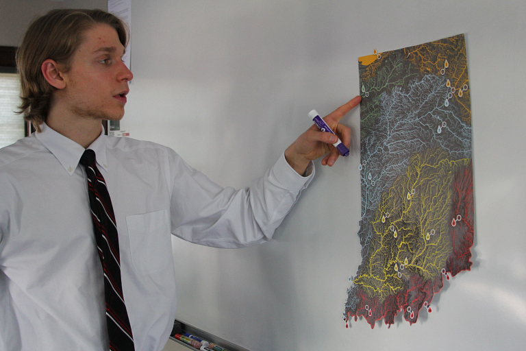 A student points to a spot on a map of Indiana