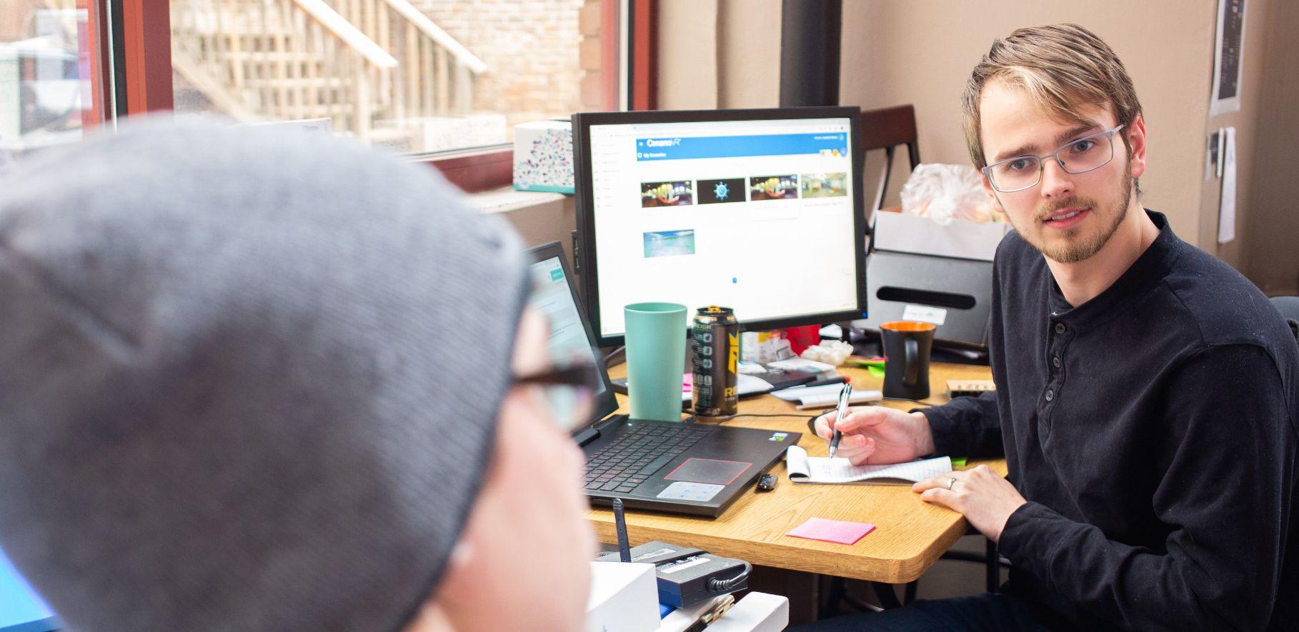 RegattaVR employees discuss a project.