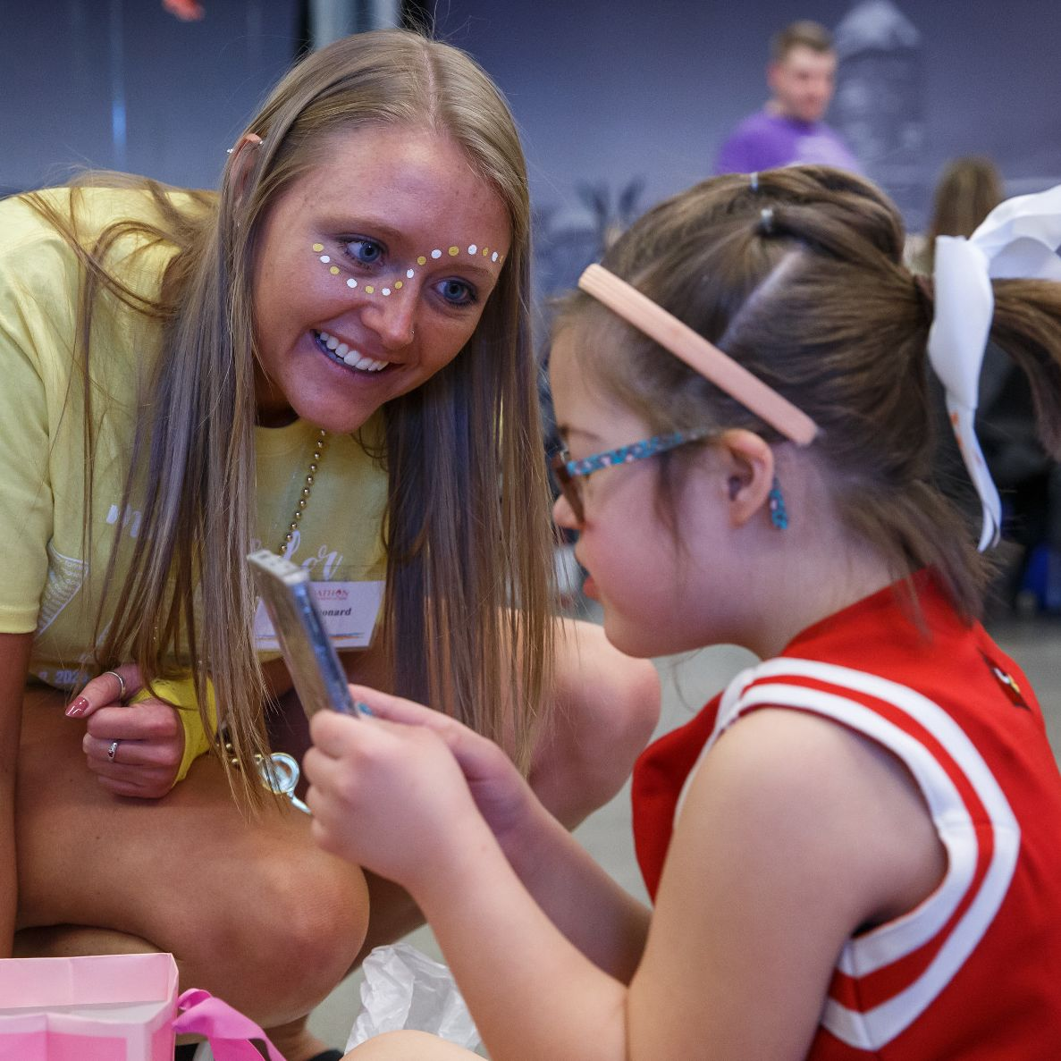 An IUPUI student wearing face paint decorations visits with a child from Riley Hospital for Children