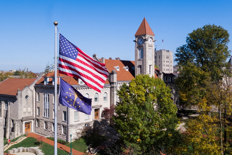 An American flag and the Indiana state flag flies over the Student Building