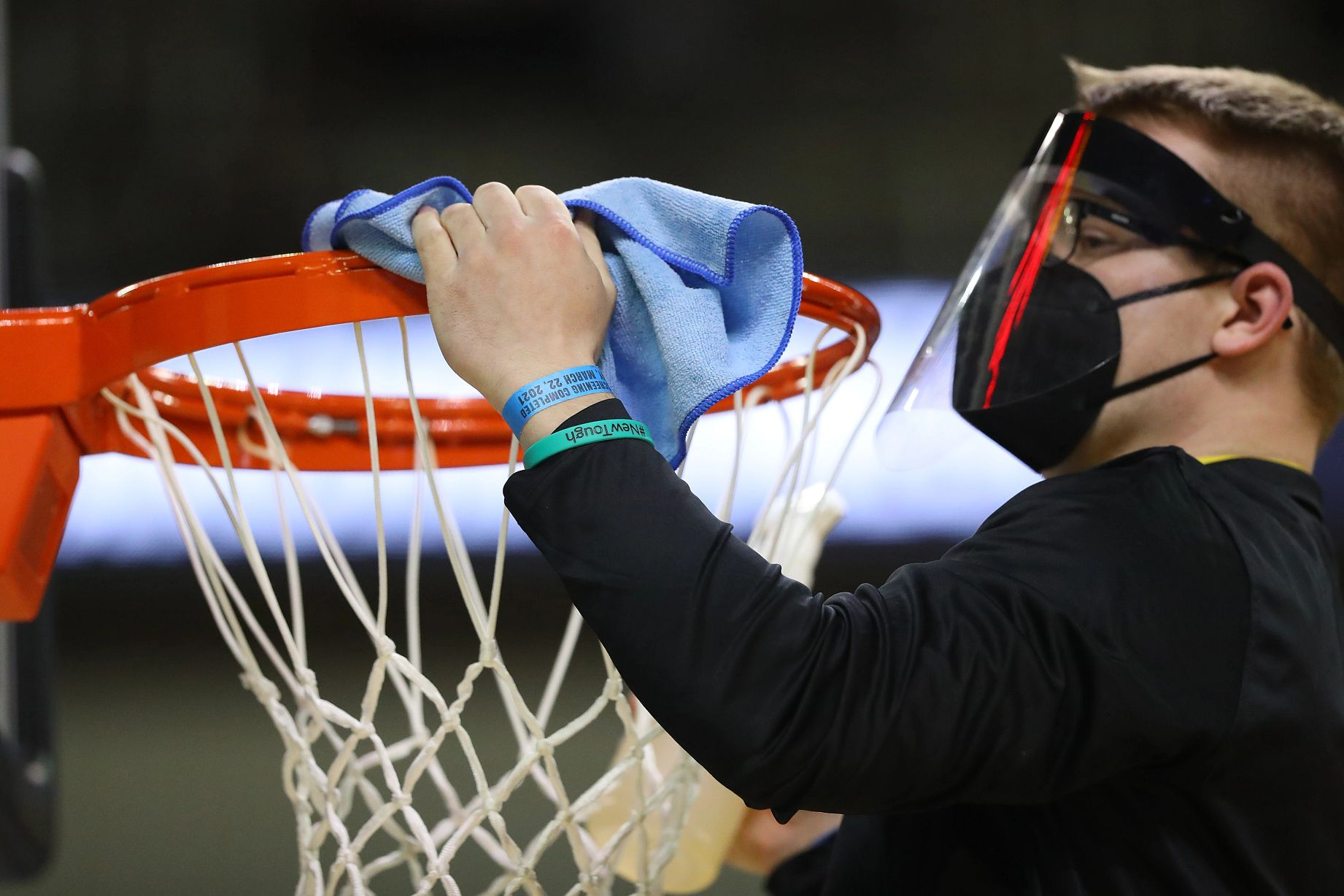 man wearing a mask and face shield wipes cleans a basketball rim