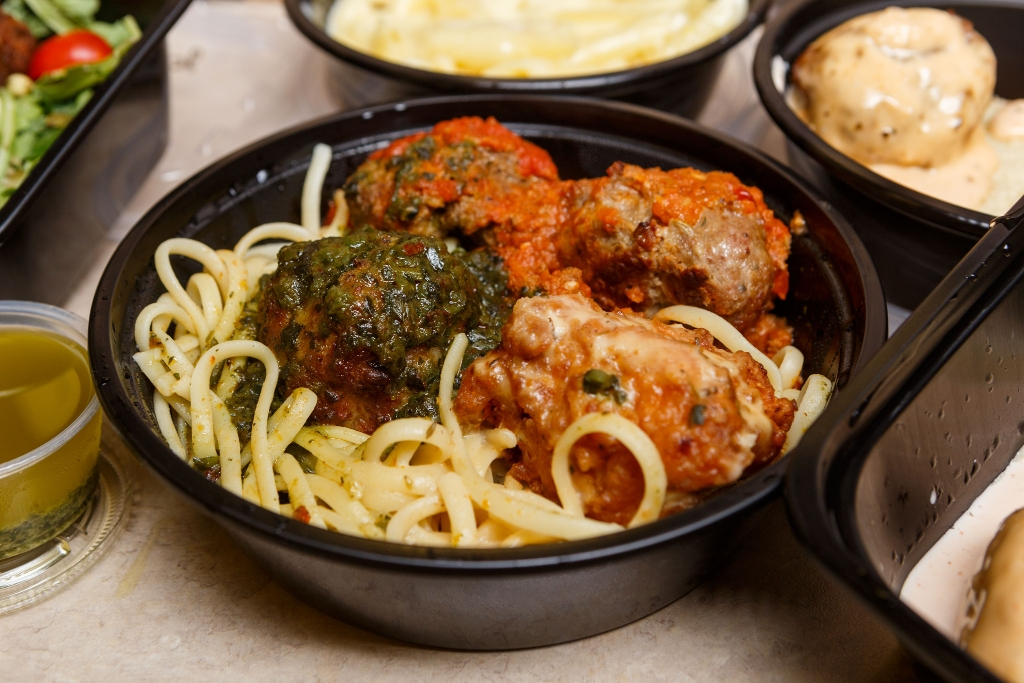 Four Mimi Blue meatballs smothered in four signature sauces, over a bed of linguine.