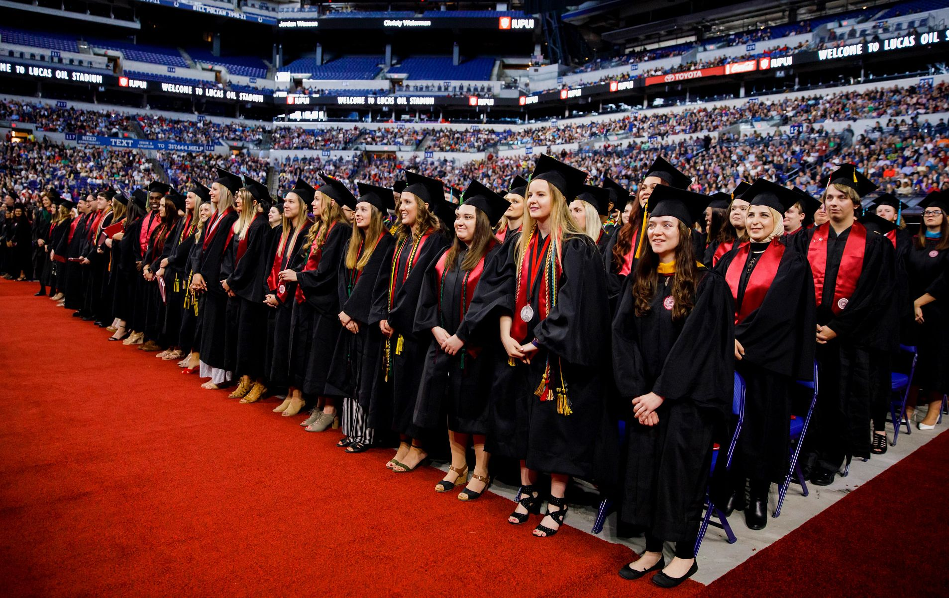 Graduates stand at Lucas Oil Stadium during an IUPUI commencement ceremony.