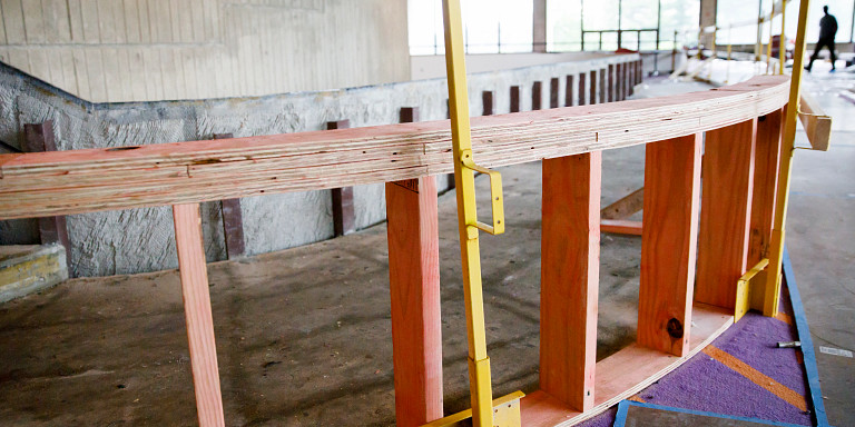 In-progress construction of accessible ramp framed to a second-floor balcony